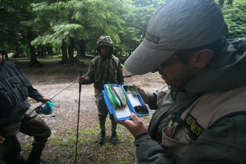 Un guía de pesca muestra las moscas al cliente. Foto: bancodepeces.es